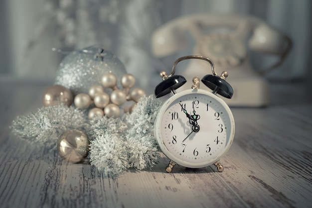 Old alarm clock showing five to midnight and white vintage phone. happy new year!