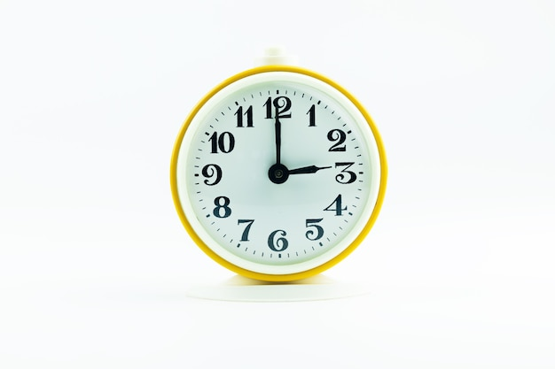 Old alarm clock shows time 15 o'clock on white isolated background