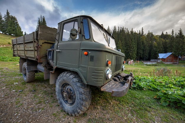 Old all terrain truck with big protector rubber tires for off road use.