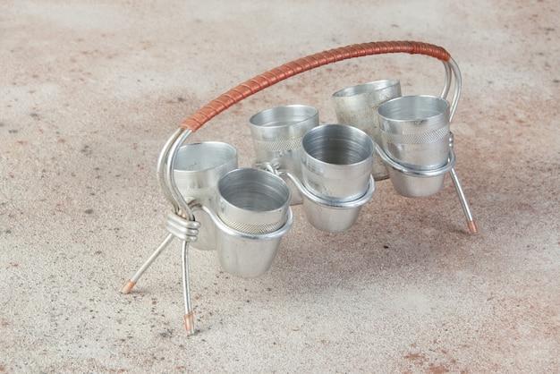 Старые алюминиевые чашки с подставкой на бетонный стол.
