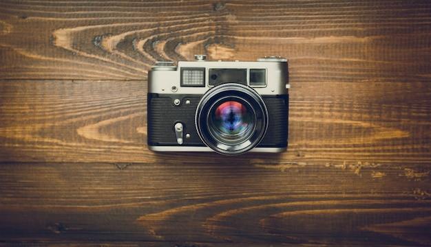 木製の背景に手動レンズを備えた古いアナログ カメラ