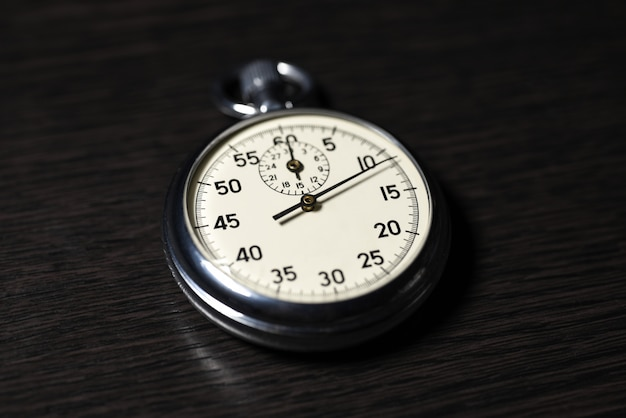 Old analog stopwatch lies on on a dark wooden surface, close-up