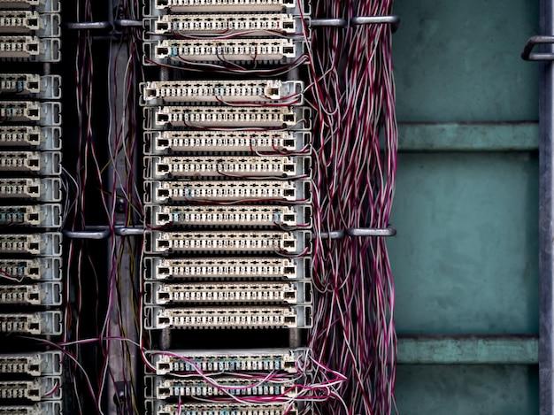 古いキャビネットのワイヤー固定ラインが付いている古いアナログ電話交換機システム接続パネル