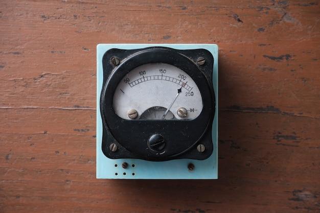 金属製の矢印が付いた古いアナログ電圧計。電気ネットワークの電圧の測定。