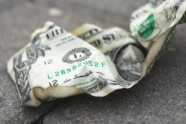 Старая и скомканная долларовая банкнота на земле