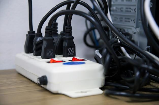 오래되고 손상된 전기 어댑터 전원 플러그에는 많은 가전 제품이 콘센트 소켓에 꽂혀 있습니다.