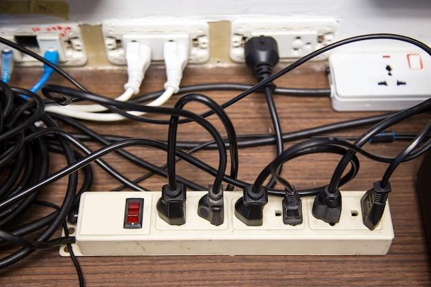 오래되고 손상된 전기 어댑터 전원 플러그에는 많은 가전 제품이 콘센트 소켓에 연결되어 있습니다.