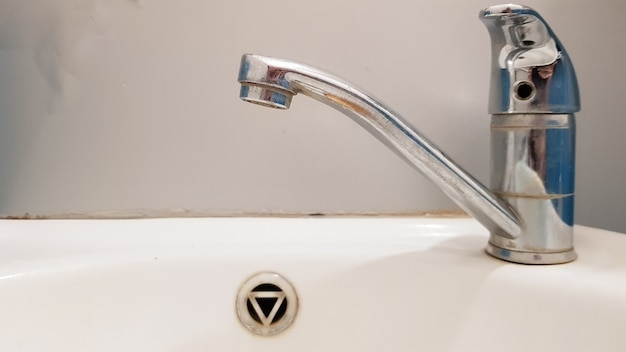 Старый и грязный кран и белая керамическая раковина для умывальника, концепция очистки, ремонта или замены ванной комнаты, туалета.