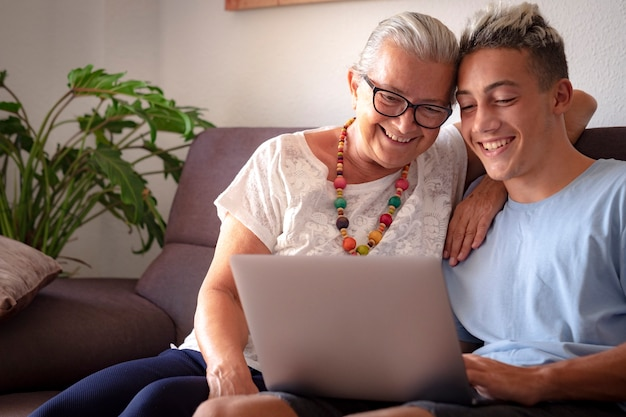 Старое и новое тысячелетнее поколение с удовольствием делят один и тот же ноутбук. бабушка и внук улыбаются счастливы, концепция любви и дружбы