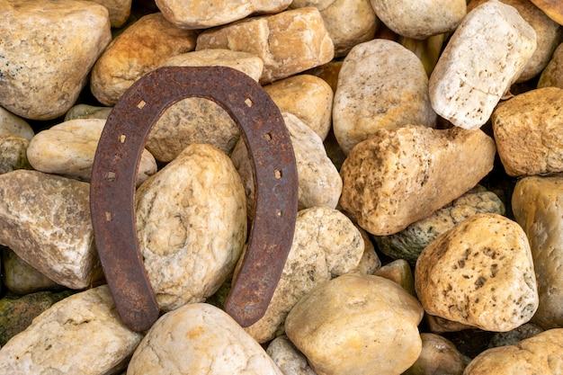 Старая и ржавая подкова посреди камней