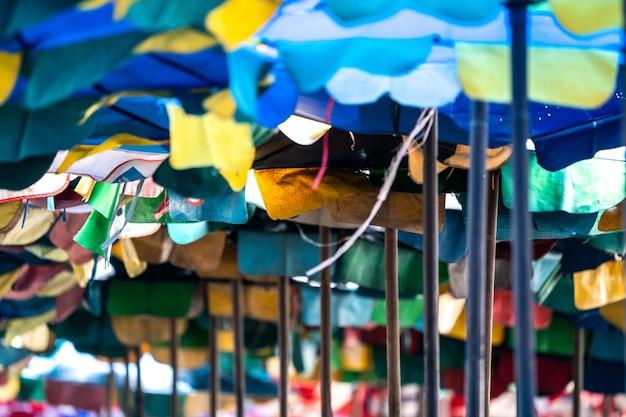 Bangsaen beach chonburi thailand에서 관광객들을 위해 햇빛을 보호하기 위해 오래되고 찢어진 우산을 엽니다.
