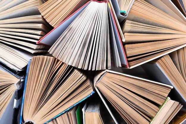 Старые и использованные книги в твердом переплете или учебники, видимые сверху.