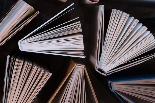 古くて使用済みのハードカバーの本、木の床の上から見た教科書。本と読書は、自己改善、私たちのキャリア、ビジネス、個人的な生活における知識と成功のために不可欠です