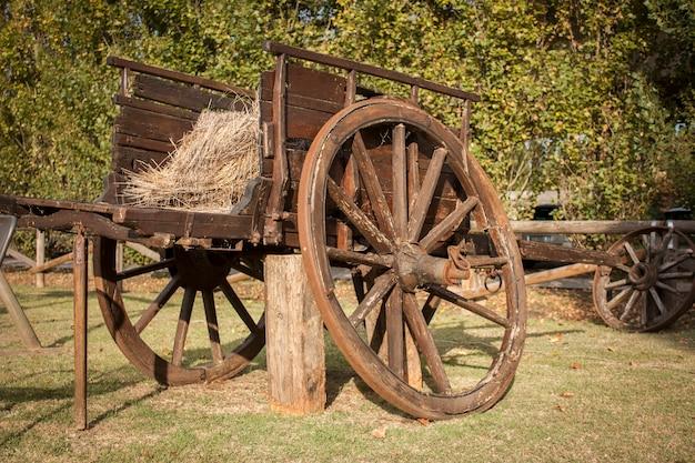 田舎の庭の装飾要素として使用される古くて使い古されたヴィンテージの木製の馬車。