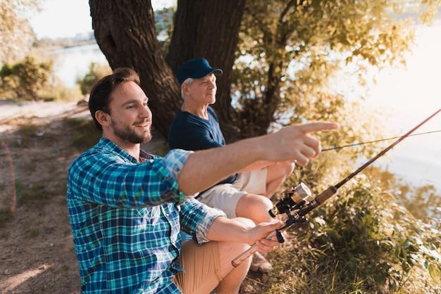 Старый и молодой парень, рыбалка с удочками.