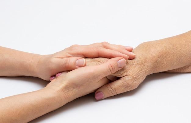 Старые и молодые руки держатся друг за друга на белом фоне