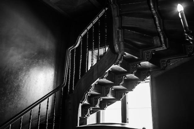 빛나는 창의 배경에 대해 위쪽으로 이어지는 오래된 골동품 나선형 계단