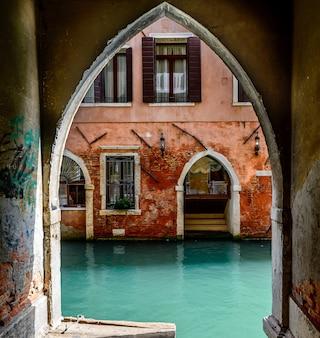 운하와 열린 창문이있는 고대 빨간 집 근처의 오래된 아치