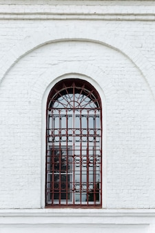 An old arched window behind bars in an old white brick building. vertical.