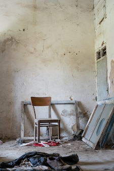 Old armchair in the middle of a room in an abandoned house