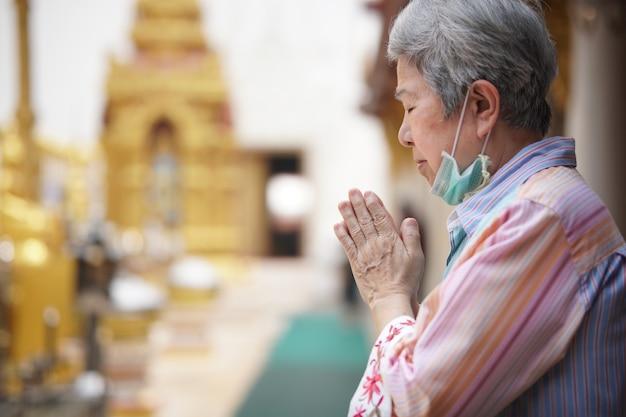 仏教寺院で祈る古いアジアの年配の女性旅行者観光客。