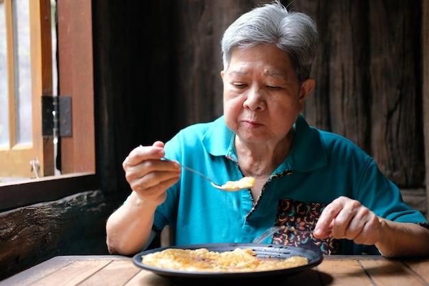 레스토랑에서 음식을 먹고 오래 된 아시아 노인 수석 노인 여자. 성숙한 은퇴 생활