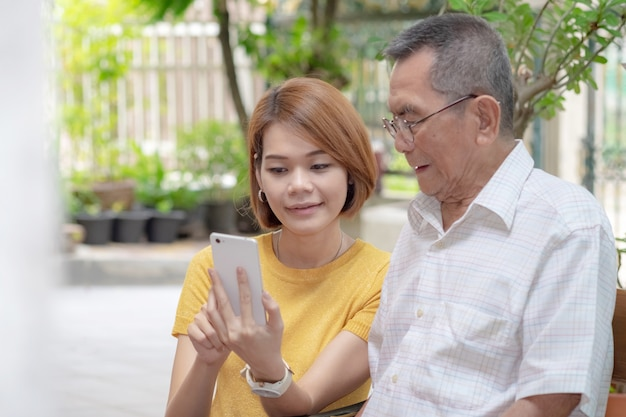Old asian father and daughter. daughter teaches an elderly father to use a mobile phone