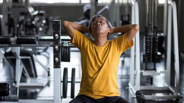 老アジア人の健康な男性は、ヨガの練習のために呼吸を吸い込んだり、運動後に休憩したり、フィットネスジムで運動したりします。高齢年金受給者のためのボディビルディングと健康的なライフスタイル。