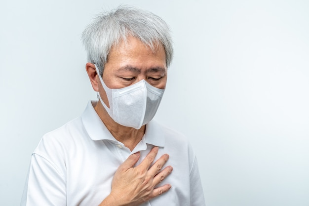 Old asian man wearing n95 mask, putting his hand on his chest, feeling sick