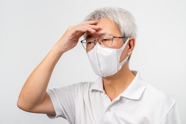 Old asian man wearing n95 mask, putting his hand on his forehead, feeling sick, white wall