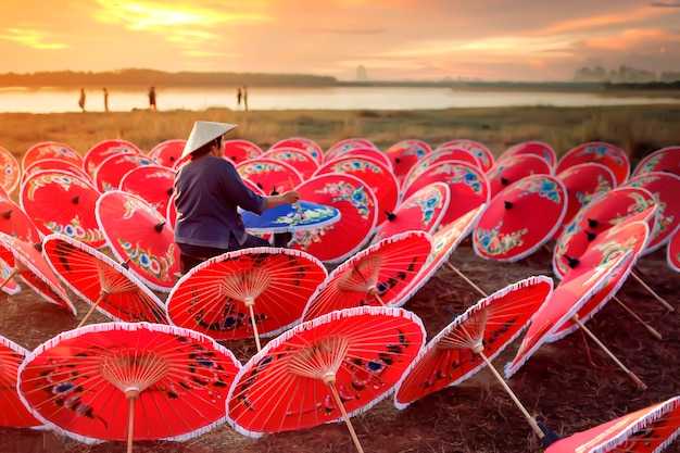 An old asian woman is painting a colorful gathering by the lake at sunset.