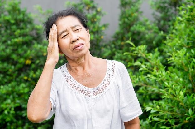 두통 편두통으로 고통받는 늙은 아시아 여성