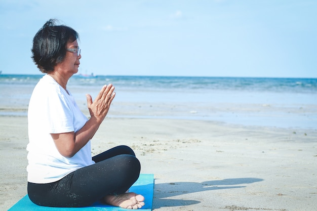 An old asian woman wearing a white shirt is doing yoga sitting on the beach.