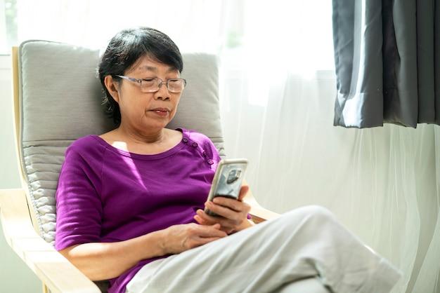 거실에서 안락의 자에 Siting 동안 오래 된 아시아 Womanusing 스마트 폰. 프리미엄 사진