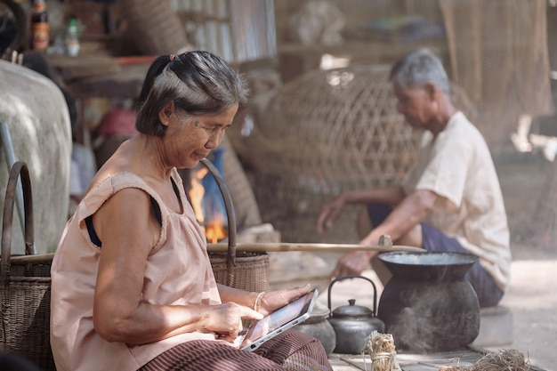 Old asian women are playing tablets in rural thailand.