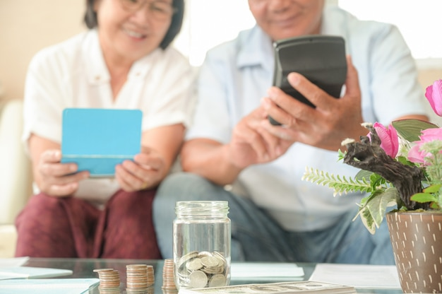 Old asian women and men sit on the sofa, they make financial plans.