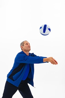Old athlete in a blue tracksuit passes ball.