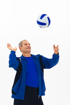 Old athlete in a blue tracksuit passes a roller ball.