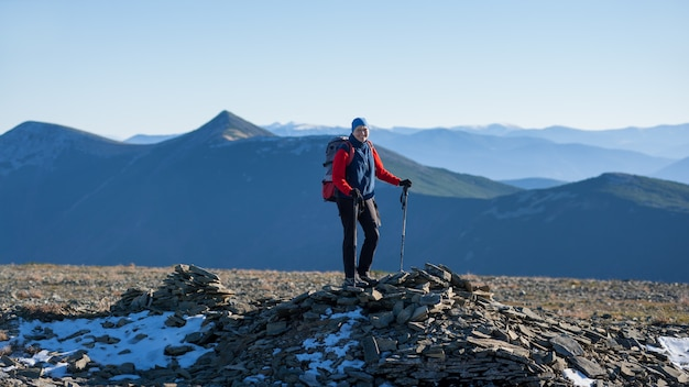 Old athletic woman backpacker standing on the top of the mountain