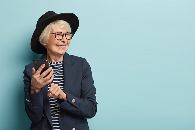Old attractive woman types text message on cellular, uses new online application, has positive facial expression, looks away, wears stylish headgear and coat, stands over blue wall, free space