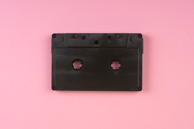 Old audio cassette on a pink.