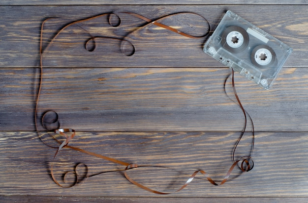 Old audio cassette tape on a brown wood