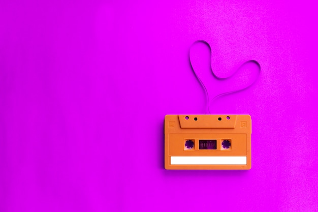 Old audio cassette tape with film shape heart on pink background.