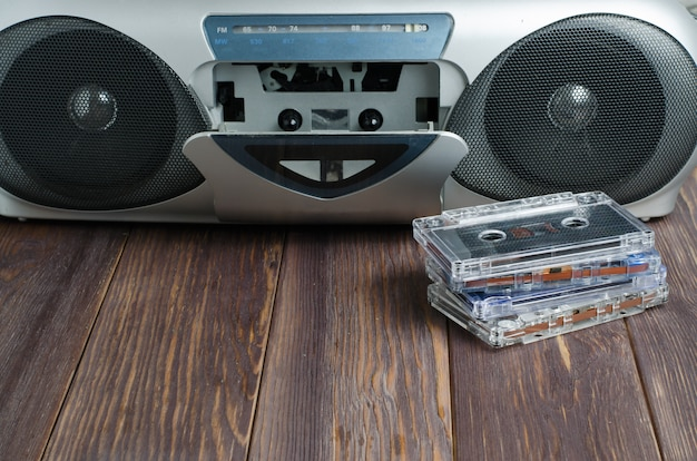 Old audio cassettes and tape recorder on wooden background