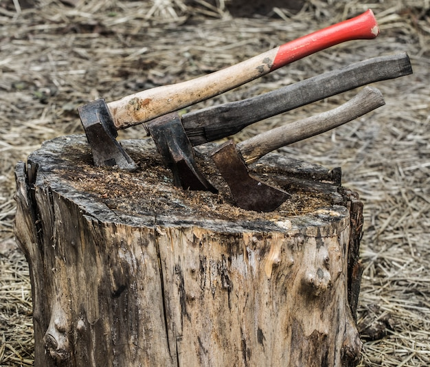 ストローの背景に切り株で立ち往生している古い斧