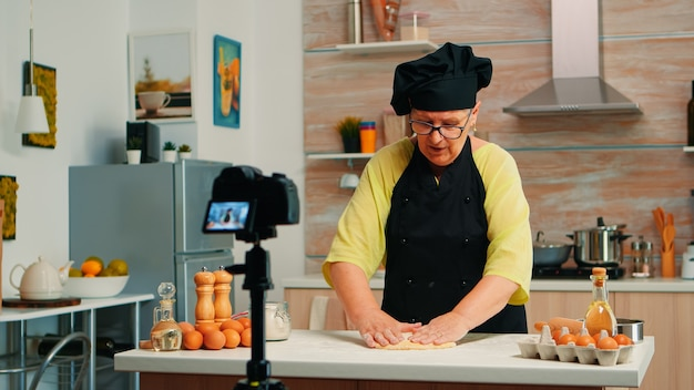 Old baker recording culinary video in kitchen preparing homemade pizza. retired blogger chef influencer using internet technology communicating shooting blogging on social media with digital equipment
