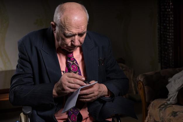 Старый лысый бизнесмен в официальной одежде, сидящий на инвалидной коляске, серьезно пишет в своей маленькой записной книжке