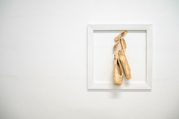 古いバレリーナの靴は、バレリーナのキャリアの記憶として、白い壁のフレームに掛けられていました