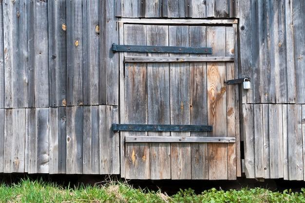 Старая стена сарая с запертой деревянной дверью
