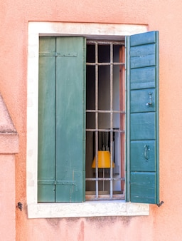 Old barred window with wooden shutters